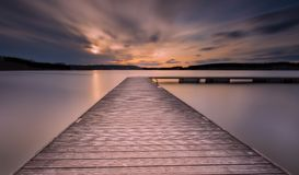 Beautiful long exposure lake with jetty at sunset. Royalty Free Stock Photos