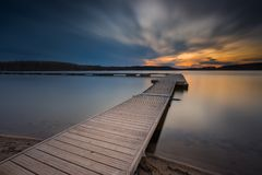 Beautiful long exposure lake with jetty at sunset. Stock Images