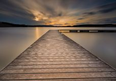 Beautiful long exposure lake with jetty at sunset. Stock Photos
