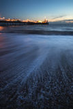 Beautiful long exposure landscape of waves receding with pier in Stock Image