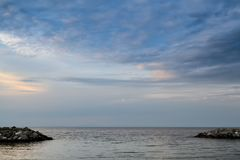 Beautiful long exposure landscapeat calm sea in the sunset. Rocky barrier near horizon Stock Photo