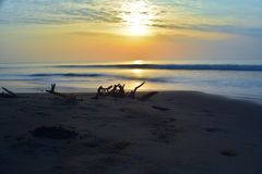 Beautiful long exposure photography of sunrise at sea shore with sea water coming over the sand