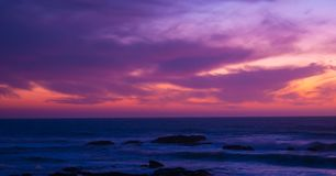 Beautiful long exposure shot over ocean at dusk just after sunset with red magenta gradient sky. And dark waves below stock image