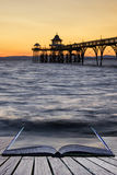 Beautiful long exposure sunset over ocean with pier silhouette c Royalty Free Stock Images