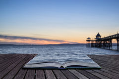 Beautiful long exposure sunset over ocean with pier silhouette c. Stunning long exposure sunset over ocean with pier silhouette conceptual book image Stock Photo