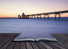 Beautiful long exposure sunset over ocean with pier silhouette c. Stunning long exposure sunset over ocean with pier silhouette conceptual book image Stock Photography