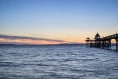 Beautiful long exposure sunset over ocean with pier silhouette. Stunning long exposure sunset over ocean with pier silhouette Royalty Free Stock Image