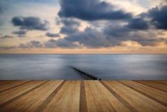 Beautiful long exposure vibrant concept image of ocean at sunset. Beautiful long exposure vibrant conceptual image of ocean at sunset with wooden planks floor stock photos