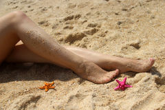 Beautiful long female legs on the beach Stock Photography