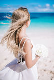 Beautiful long hair bride in long white dress standing on the beach with white bouquet looking to the sea stock images