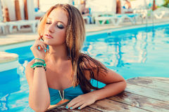 Beautiful long hair female model posing by the pool, outdoor por Stock Photos