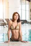 Beautiful long hair female model posing by the pool stock photography