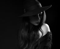 Beautiful long hair woman posing in black shirt and fashion eleg. Ant hat in dramatic light on dark shadow background. Closeup art portrait. Black and white Royalty Free Stock Photography