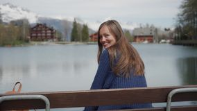 Beautiful long-hair woman sitting back on wooden bench at lakeside with scenic mountain view. Then girl looking back and. Smiling beautifully to the camera 4k stock video footage