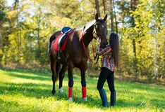 Beautiful long hair young woman with a horse outdoor Stock Photo