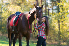 Beautiful long hair young woman with a horse outdoor Stock Photography