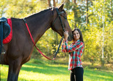 Beautiful long hair young woman with a horse outdoor Royalty Free Stock Photos