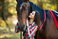 Beautiful long hair young woman posing with a horse outdoor Royalty Free Stock Photography