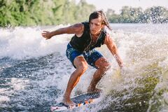 Beautiful long haired blond wakesurf in vest on board along waves of lake. Athletic male athlete wakes surfing in summer on river. Wakesurf water sport. Surfer