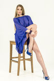 Beautiful long-haired blonde in a clear blue tunic and blue shoes Royalty Free Stock Photos