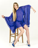 Beautiful long-haired blonde in a clear blue tunic and blue shoes Stock Image