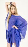 Beautiful long-haired blonde in a clear blue tunic and blue shoes Stock Images