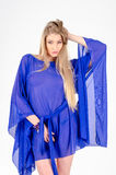Beautiful long-haired blonde in a clear blue tunic and blue shoes Stock Photography