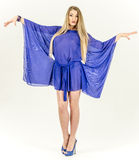 Beautiful long-haired blonde in a clear blue tunic and blue shoes Stock Photo