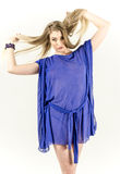 Beautiful long-haired blonde in a clear blue tunic and blue shoes Royalty Free Stock Photo