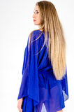 Beautiful long-haired blonde in a clear blue tunic and blue shoes Royalty Free Stock Photography