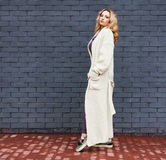 A beautiful long-haired blonde girl posing in a trendy white knitted long coat near a gray brick wall. Fashion Style Royalty Free Stock Photography