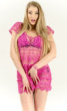 Beautiful long-haired blonde in a pink dress standing lush, flirty skirt lifting Royalty Free Stock Photography