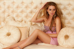 Beautiful long-haired blonde sitting on a bed with pillows in pink evening dress Royalty Free Stock Photos