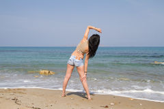 Beautiful long haired brunette in beachwear exercising at the be Royalty Free Stock Photo