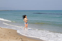 Beautiful long haired brunette in beachwear jogging at the beach Royalty Free Stock Photography