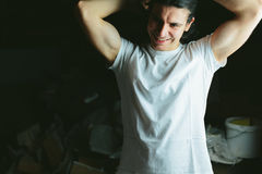 Beautiful long haired brunette guy hands behind his head in white t-shirts Royalty Free Stock Photos
