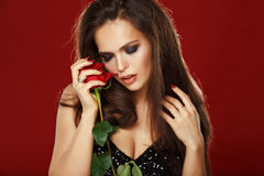 Beautiful long-haired brunette holding a red rose. Studio, dark Royalty Free Stock Photos