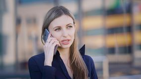 Beautiful long-haired business woman is standing in the street near office building and speaking on the phone. Female. Sales manager is working outside with stock video footage