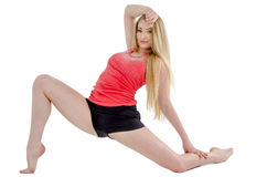 Beautiful long-haired cheerful girl is engaged in gymnastic exercises on the floor Royalty Free Stock Photography