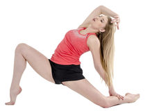 Beautiful long-haired cheerful girl is engaged in gymnastic exercises on the floor Royalty Free Stock Photo