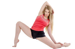 Beautiful long-haired cheerful girl is engaged in gymnastic exercises on the floor Royalty Free Stock Image