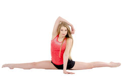 Beautiful long-haired cheerful girl is engaged in gymnastic exercises on the floor Royalty Free Stock Images