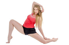 Beautiful long-haired cheerful girl is engaged in gymnastic exercises on the floor Stock Photography