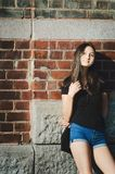 Beautiful long-haired girl on a brick wall background. The concept of a lonely woman stock images