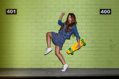 Beautiful long-haired girl with a color penny shortboard near a Stock Photo