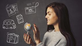 The Destination Chosing. Beautiful long-haired girl is holding small globe on grey background with travel icons, destination chosing concept Stock Image
