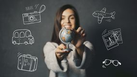 The Destination Chosing. Beautiful long-haired girl is holding small globe on grey background with travel icons, destination chosing concept Stock Photo