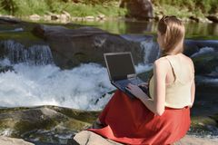 Beautiful long-haired girl in red skirt with laptop sitting on a rock on a background of mountain river cascade. Freelance concept stock images