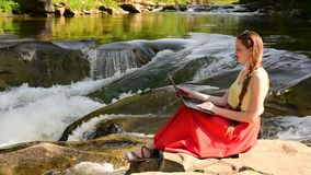 Beautiful long-haired girl in red skirt with laptop sitting on a rock on a background of mountain river cascade. Freelance concept. Work in nature stock video footage