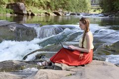 Beautiful long-haired girl in red skirt with laptop sitting on a rock on a background of mountain river cascade. Freelance concept royalty free stock photos